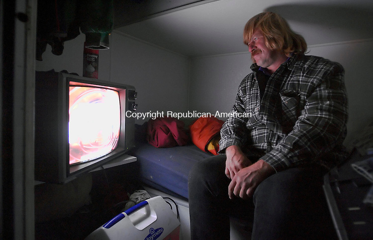 BETHLEHEM, CT -  - 10 SEPTEMBER 2005 -091005JS03--[2:10 am] Carnival worker Chris Constantine of Fitchburg, MASS., watches television inside his sleeping quarters at the Bethlehem Fair. Constantine sleeps in a unit of a trailer that houses 8 units and two showers. <br /> Jim Shannon / Republican-American