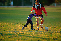 Father and son playing soccer.