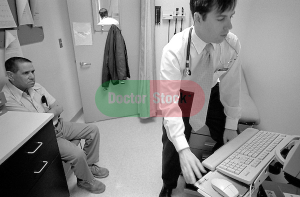 Elderly male patient watches male doctor at computer in examination room