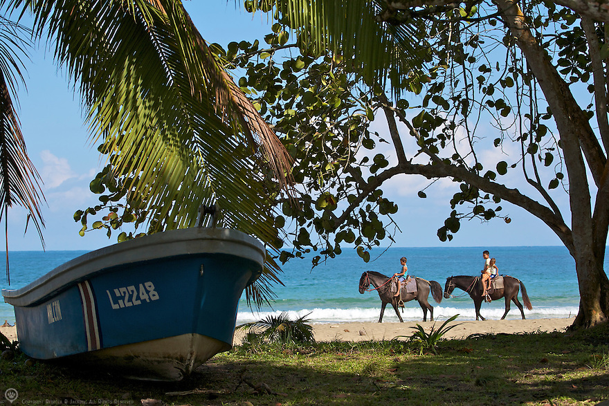 Children riding horses on a beach in Costa Rica