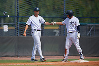 GCL Yankees East manager Dan Fiorito (27) fist bumps Raymundo Moreno (5) after a triple during a Gulf Coast League game against the GCL Phillies East on July 31, 2019 at Yankees Minor League Complex in Tampa, Florida.  GCL Yankees East defeated the GCL Phillies East 11-0 in the first game of a doubleheader.  (Mike Janes/Four Seam Images)