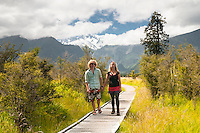Tourists on walking track at Lake Matheson with mountains in background, Westland NP, West Coast, New Zealand