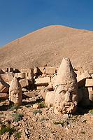 Statue head of Herakles & Apollo (behind) in front of the stone pyramid 62 BC Royal Tomb of King Antiochus I Theos of Commagene, west Terrace, Mount Nemrut or Nemrud Dagi summit, near Adıyaman, Turkey