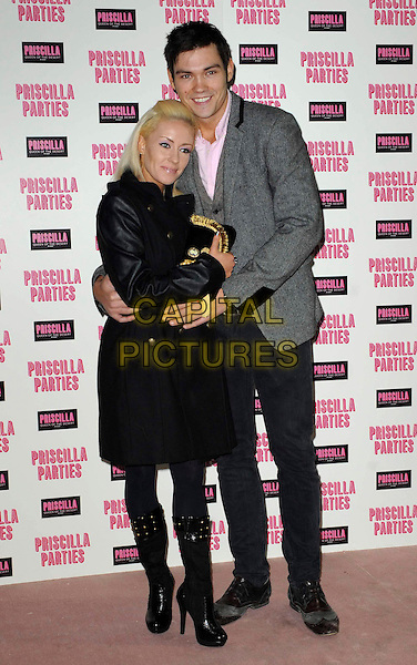 BRIANNE DELCOURT & SAM ATTWATER.The launch of 'Priscilla Parties' at the Palace Theatre, London, England, UK, January 24th 2011.full length grey gray jacket blazer black coat clutch bag arms around pink shirt .CAP/DS.©Dudley Smith/Capital Pictures