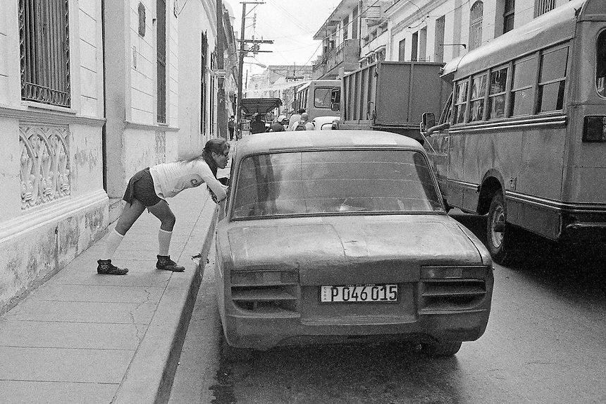 A woman stops to chat during a traffic jam in Santa Clara, Cuba. MARK TAYLOR GALLERY
