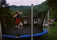 Children play on a trampoline outside their trailer protected by the hills where their family moved. The mountains have been a source of work and a quiet place to raise families.