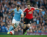 Sergio Aguero of Manchester City battles Daley Blind of Manchester United during the Barclays Premier League match at the Etihad Stadium. Photo credit should read: Philip Oldham/Sportimage