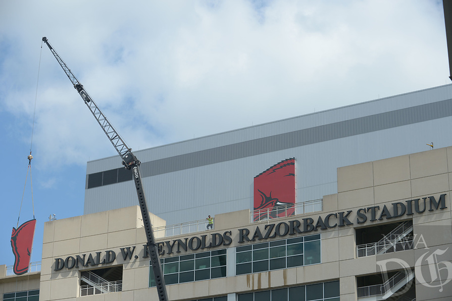 NWA Democrat-Gazette/ANDY SHUPE<br /> Workers with Multi-Craft Contractors and Sign Studio work to guide a panel of a large Razorback mascot logo Thursday, Aug. 9, 2018, onto the south side of Razorback Stadium in Fayetteville. The sign is being attached to the large video screen as a part of a renovation to the stadium.