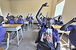 A boy--with a shirt sporting Barack Obama--raises his hand during class in a school in the Southern Sudanese village of Kenyi. The school was constructed by the United Methodist Committee on Relief (UMCOR).  Families here are rebuilding their lives after returning from refuge in Uganda in 2006 following the 2005 Comprehensive Peace Agreement between the north and south. NOTE: In July 2011, Southern Sudan became the independent country of South Sudan
