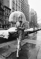 June 1971, New York City, New York State, USA --- Transparent umbrellas are becoming the hottest fashion accessory in New York. Their practical transparent surround and mushroom shape without the classic protruding spikes makes them less dangerous than their predecessors. They are also a great boon for glasses wearers and women's hairstyles, especially on windy days. --- Image by © JP Laffont/Sygma/Corbis