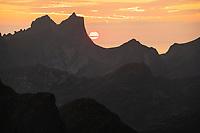 Setting summer sun behind the rugged mountain peaks of Moskenesøy, Lofoten Islands, Norway