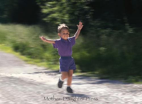 Small boy running down road in joy