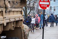 """People line up as Army National Guard soldiers (181st Engineer) hand out food and care packages to residents of Chelsea, Massachusetts, at the intersection of Congress Avenue and Hawthorne Street in Chelsea, Massachusetts, on Mon., April 27, 2020. The operation is part of daily pop-up food distribution in the city as part of relief efforts during the ongoing Coronavirus (COVID-19) global pandemic. Chelsea, Mass., is one of the hardest hit communities in Massachusetts with high infection and death rates. As much as 80% of the population works in so-called """"essential jobs,"""" meaning that they continue to work during shelter-in-place orders."""