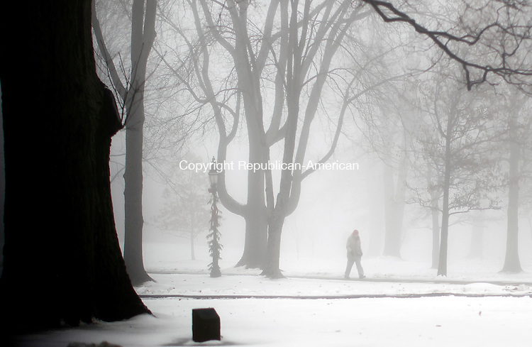Litchfield, CT- 05 January 2015-010415CM02-  Dense fog encompasses a man while walking through the Litchfield Green on Sunday morning.  According to the National Weather Service,  Monday is expected to be mostly sunny with a high near 28F.  Christopher Massa Republican-American