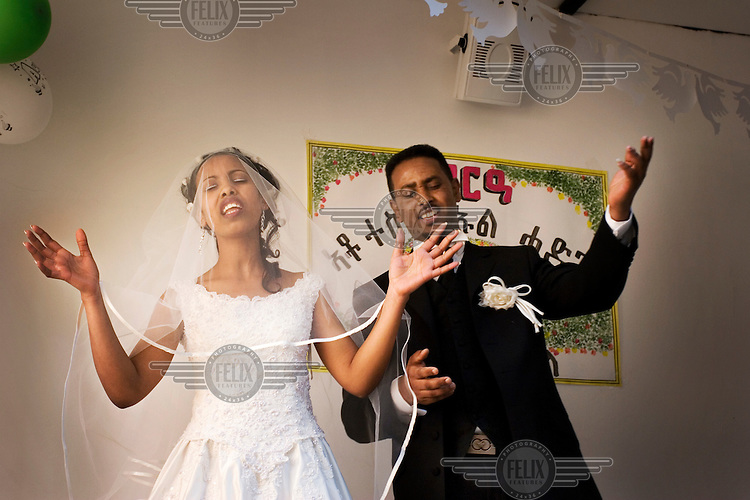 A young Eritrean-Ethiopian couple sing during their wedding celebrations at an Evangelical Christian church in Palermo. .