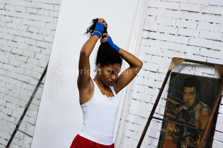 Laura Astudillo, a young Colombian boxer, ties hair into a ponytail before a sparring session in the boxing gym in Cali, Colombia, 18 April 2013. During the recent years, Kina Malpartida, a Peruvian female professional boxer, has won the World Championship title several times and so she has become a sporting idol and an inspiration for a generation of young girls throughout Latin America. Working out hard in poorly equipped gyms, they dream of becoming a boxing star. The Cauca Valley and the Caribbean coast are believed to be a home of the most talented female boxers in Colombia.