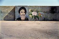 An image of Ayatollah Khomeini and some flowers on a wall.