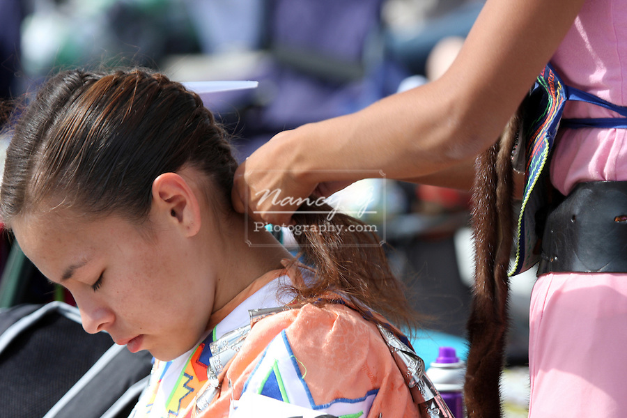 Two teenager girls braiding hair into braids at a Pow Wow at the Milwaukee Lakefront Indian Summer Festival, Wisconsin