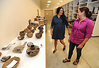 NWA Democrat-Gazette/ANDY SHUPE<br /> Carrie Wilson (center), a representative of the Quapaw tribe, speaks Wednesday, June 7, 2017, with Sarah Shepard, a research associate with the University of Arkansas, about a collection of funerary pottery from around the year 1200 at the University of Arkansas Archeological Survey in Fayetteville. The survey has repatriated items recovered from sites in Arkansas to the Quapaw and Caddo tribes.