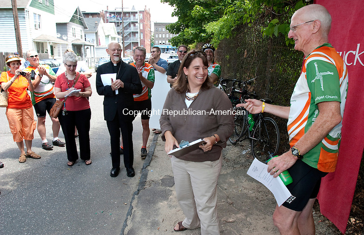 WATERBURY, CT. 29 June 2010-062910SV03--Cori Thibodeau, executive director, Office For Catholic Social Justice Ministries, jokes with Bob King of Brake the Cycle of Poverty, during a ceremony ending a 6 day ride by a group of riders ending on Jewelry Street in Waterbury Tuesday. The Naugatuck Valley Project hosted the riders from &quot;Brake The Cycle of Poverty&quot; who are raising awareness in the state.<br /> Steven Valenti Republican-American
