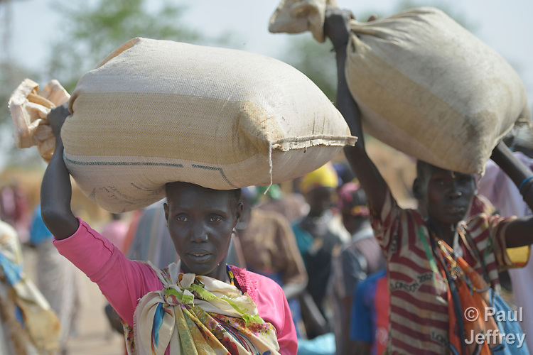Displaced women carry bags of sorghum that they received April 7, 2017, in Rumading, a village in South Sudan's Lol State where more than 5,000 people, chased from their homes by drought and conflict, remain in limbo. In early 2017, they set out walking for Sudan, seeking better conditions, but were stopped from crossing the border. They remained camped out under the trees at Rumading, eating wild leaves as the rainy season approached.<br /> <br /> In early April, Norwegian Church Aid, a member of the ACT Alliance, began drilling a well in the informal settlement and distributed sorghum, beans and cooking oil to the most vulnerable families. The ACT Alliance is carrying out the emergency assistance in coordination with government officials and the local Catholic parish.