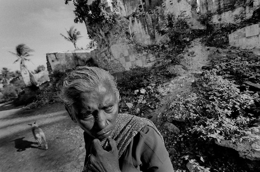 A Tamil woman walks through a neighborhood destroyed by shelling in Jaffna, Sri Lanka, Friday, Oct. 19, 2007.