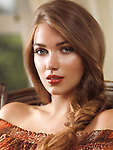 Artistic portrait of a young beautiful woman with long light brown braided hair sitting in a chair