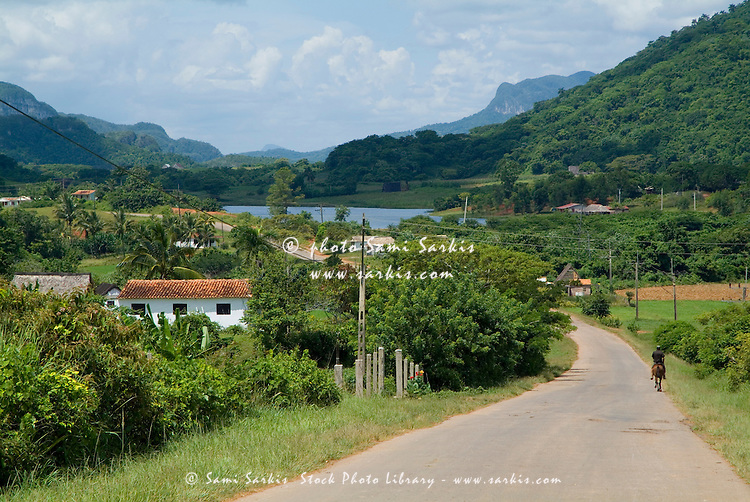 Man riding his horse along a rural road in the Vinales Valley, Cuba.