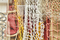 Fishing net's on display in a shop window, yellow and white net's hanging with red and brown canvas as backdrop.