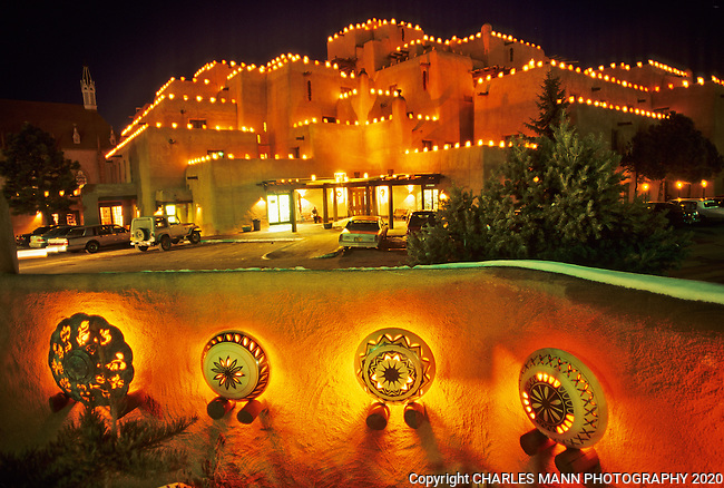The roof of the Inn at Loretto in  Santa Fe is brightened on Christmas Eve by hundreds of  faralitos, often called luminarias, along with pretty pottery-themed light fixtures.