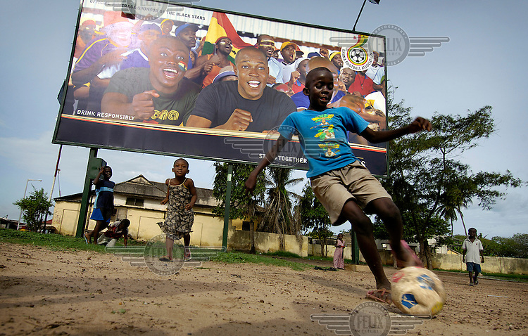 Children from a poor neighbourhood play football beneath a Guinness advertisement picturing the Ghanaian national football team, the Black Stars.