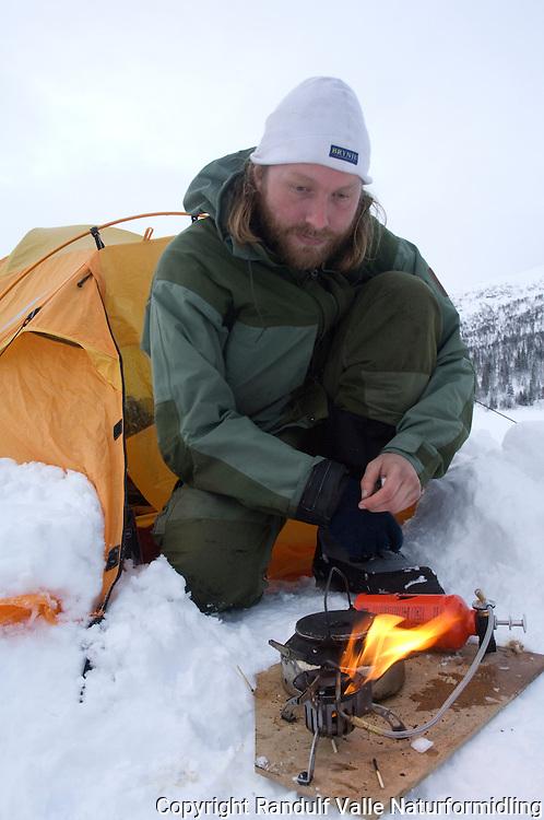 Mann forvarmer primus utenfor telt ---- Man priming stove outside tent