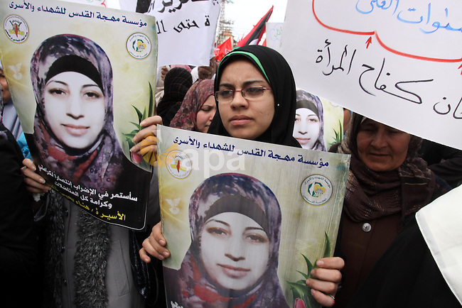 """Palestinian women demonstrate in solidarity with Hana'a Shalabi during a protest in Gaza City, on Mar. 12, 2012. Shalabi, released by Israel in a prisoner swap last year but re-arrested earlier this month and held without charge, is on a hunger strike to protest her treatment, officials said. The Arabic writing on the sign reads ''Down with administrative detentions"""". Photo by Mohammed Asad"""