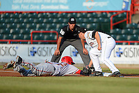 Erie Seawolves first baseman James Robbins #21 attempts to tag Brian Goodwin #23 diving back to first as umpire Billy Cunha looks on during a game against the Harrisburg Senators on July 2, 2013 at Jerry Uht Park in Erie, Pennsylvania.  Erie defeated Harrisburg 2-1.  (Mike Janes/Four Seam Images)