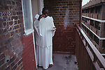Home Meeting, in the district of  Elephant and Castle, South London. UK. Church members  have gone to bless this apartment, that a members has just rented.  The apartment is being blessed holy water sprinkled in all the rooms and on the landing. The Church of the Brotherhood of the Cross and Star. A Nigerian church in Britain. This semi Christian church was founded by Olumba Olumba Obu known as OOO. His members worship him and Christ. He believes that he is the eighth and final reincarnation of the Godhead.