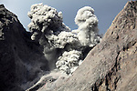 Ash cloud from explosive strombolian eruption rising from active crater of Batu Tara Volcano, Komba Island, Indonesia.