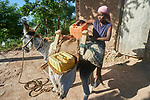 Rose Marie Pierre loads her donkey in Picmy, a village on the Haitian island of La Gonave where Service Chrétien d'Haïti is working with survivors of Hurricane Matthew, which struck the region in 2016. SCH, a member of the ACT Alliance, supports agriculture on the island by providing tools, seeds, and technical support and training for farmers. It also provided donkeys to many families. In Pierre's case, the donkey helps her bring water from a long distance to her family.