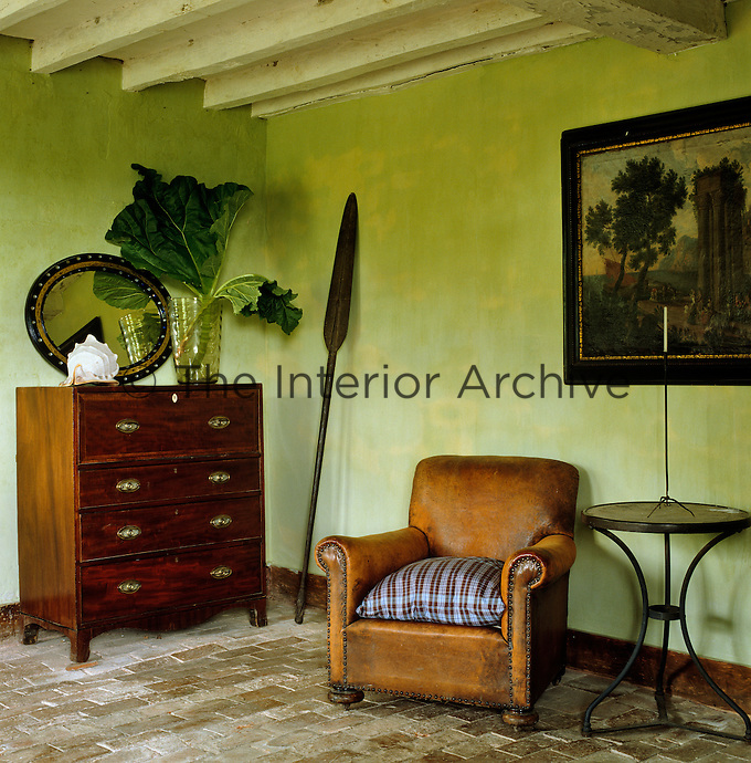 A worn leather armchair and a mahogany chest of drawers in a green country living room