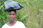A woman carries a bag on her head in Mount Barclay, Liberia.