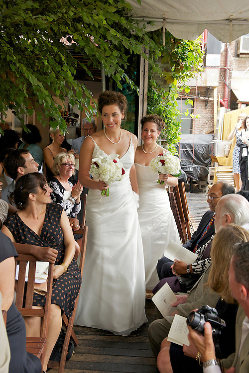 The two brides walking down the aisle.