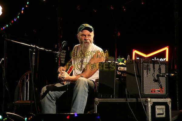 SEASICK STEVE.Live at the Hammersmith Apollo, London, England..January 31st, 2009.half length stage concert gig performance music beard facial hair green baseball cap hat white tank top guitar singing tattoos sitting full jeans denim .CAP/MAR.©Martin Harris/Capital Pictures.