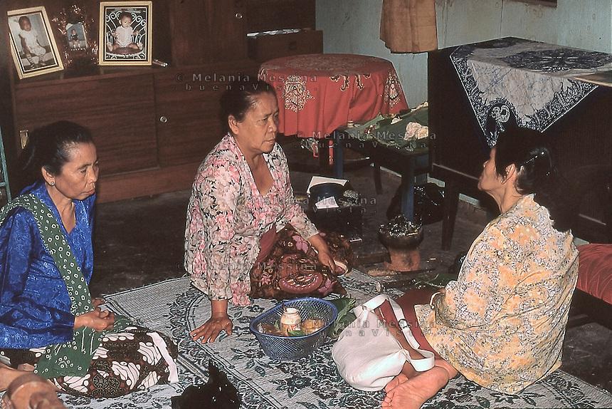 The shaman duk&ugrave;n Ibu Mul receives two women looking for her help.<br /> La sciamana duk&ugrave;n Ibu Mul riceve due donne che richiedono la sua consulenza.