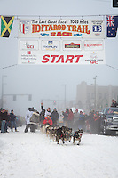 Travis Beals and team leave the ceremonial start line at 4th Avenue and D street in downtown Anchorage during the 2013 Iditarod race. Photo by Jim R. Kohl/IditarodPhotos.com