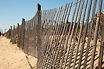 A fence lines the boardwalk and keeps visitors off the nearby dunes at Rehoboth Beach, Delaware, USA.