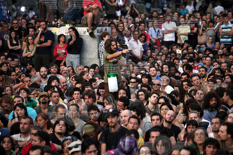A young man stands above the crowd spraying everyone with water. In May 2012, following a worsening financial crisis and a deepening recession in Spain, thousands of people started to gather in Spanish cities to protest against austerity, the global financial system, high unemplyment rate (Spain's is the highest rate in Europe) and the lack of opportunities. The protest movement has become known as 'los indignados' (the indignant ones).