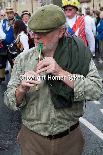 Man playing a Penny whistle.   Uppermill Saddleworth Yorkshire Uk.