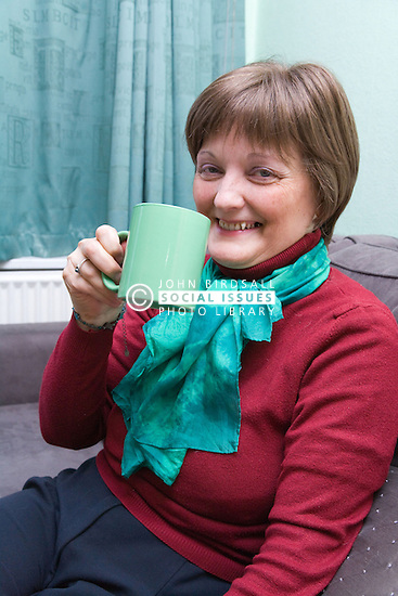 Woman; who has been undergoing Chemotherapy treatment for breast cancer; sitting at home drinking a mug of tea,
