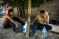 ARRIAGA, MEXICO - NOVEMBER 08: (L) Migrant Walter Martinez, 28, checks in on the health of fellow Honduran Josue Carillas Carnelas, 30, as they take a break en-route from Arriaga to Chahuites, on the 8th of November, 2015 in Arriaga, Mexico. <br /> <br /> Daniel Berehulak for The New York Times