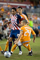 CD Guadalajara forward Sergio Santana (21) is held up by Houston Dynamo midfielder Geoff Cameron (20) and Dynamo defender Wade Barrett (24) during the group stage of the Superliga 2008 tournament at Robertson Stadium in Houston, TX on July 15, 2008.