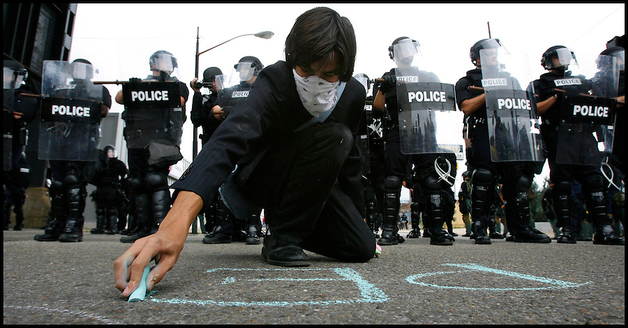 "Sept. 24,  - Pittsburgh, Pennsylvania, USA - .A protester writes ""Peace"" with sidewalk chalk in front of a line of riot police gathered near downtown Pittsburgh, PA Thursday near the site of the G-20 Summit. Brian Blanco/ZUMA Press"